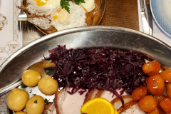 Traditional Danish dinner consisting of roast pork, boiled and sugar-browned potatoes, pickled red cabbage, cream gravy, and hash